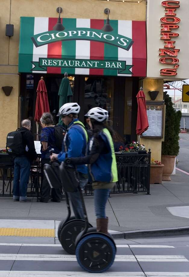 Visitors riding Segways make their way past Cioppino's restaurant, which has become a Fisherman's Wharf mainstay. Photo: Andre Zandona, The Chronicle