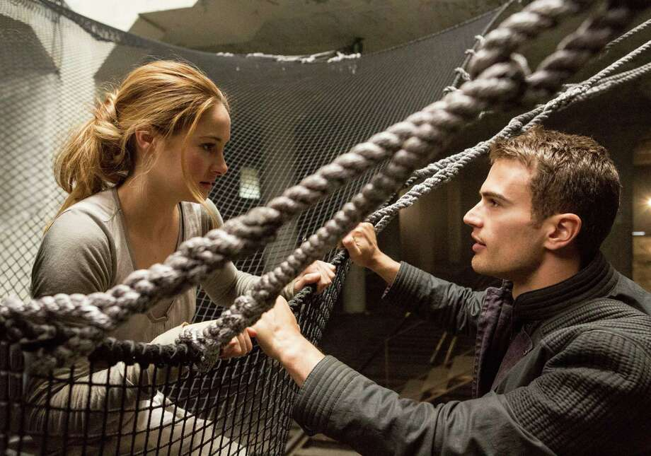 "This image released by Summit Entertainment shows Shailene Woodley, left, and Theo James in a scene from ""Divergent."" The movie releases on Friday, March 21, 2014. (AP Photo/Summit Entertainment, Jaap Buitendijk, file)  ORG XMIT: CAET899 Photo: Jaap Buitendijk / Summit Entertainment"