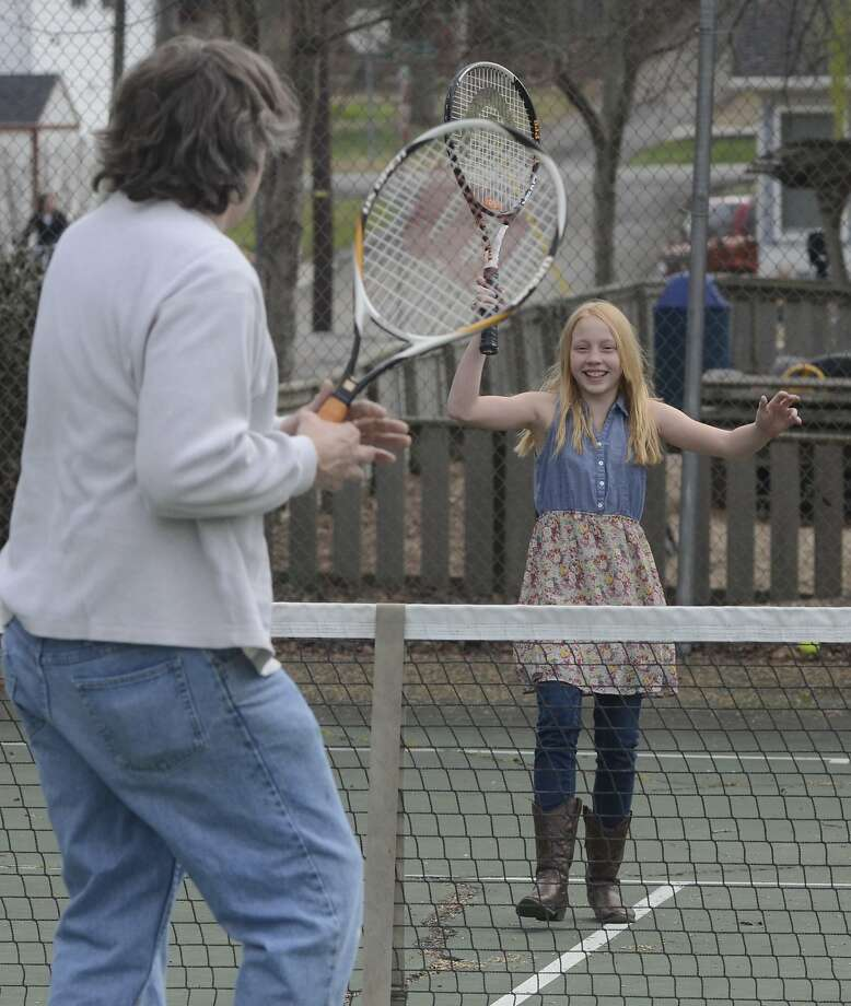 But, Dad, it's more fun with a ball:Michael Brumlow plays tennis with his    10-year-old daughter, Mallory, at Deer Park playground in Cleveland. Nice tennis boots, Mallory! Photo: John Rawlston, Associated Press