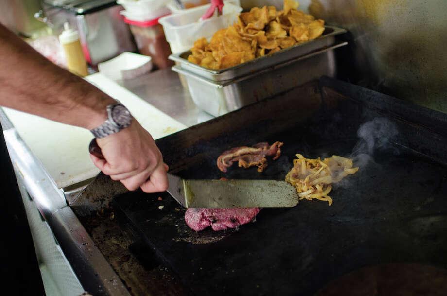 "Don Schoenburg preparing a Gastro ""Punk"" Burger. Photo: Jamaal Ellis, For The Chronicle / ©2013 Houston Chronicle"