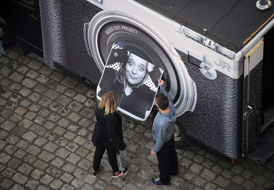 So flattering! A teenager looks at her portrait after she was photographed in the truck of French street artist and photographer JR in La Rochelle, France. Photo: Xavier Leoty, AFP/Getty Images