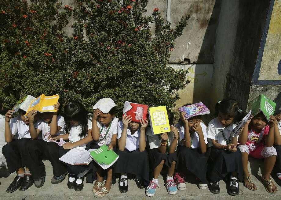 Some call them books, we call them reading helmets: Filipino pupils cover their heads during a nationwide earthquake drill in Quezon city, Philippines. Their school, Bagong Silangan Elementary, sits near a fault line. Photo: Aaron Favila, Associated Press
