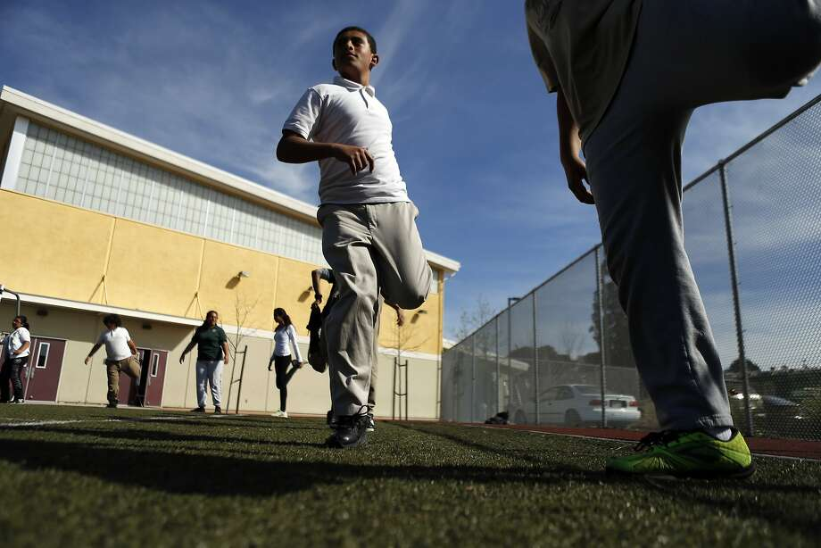 Naji Algaal stretches with his classmates as part of their race preparation. Photo: Carlos Avila Gonzalez, The Chronicle
