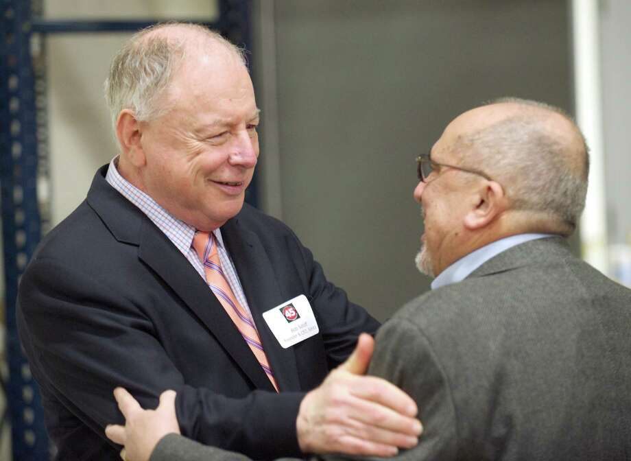 Robert Soloff, CEO and founder of Sonics & Materials, Inc., greets past employee Bob Bongo during a party held to celebrate the 45th anniversary of its founding at its Newtown, Conn building, on Thursday March 20, 2014. Bongo was and Executive Vice President in the early 1970's, working for the company for 12 years. Photo: H John Voorhees III / The News-Times Freelance