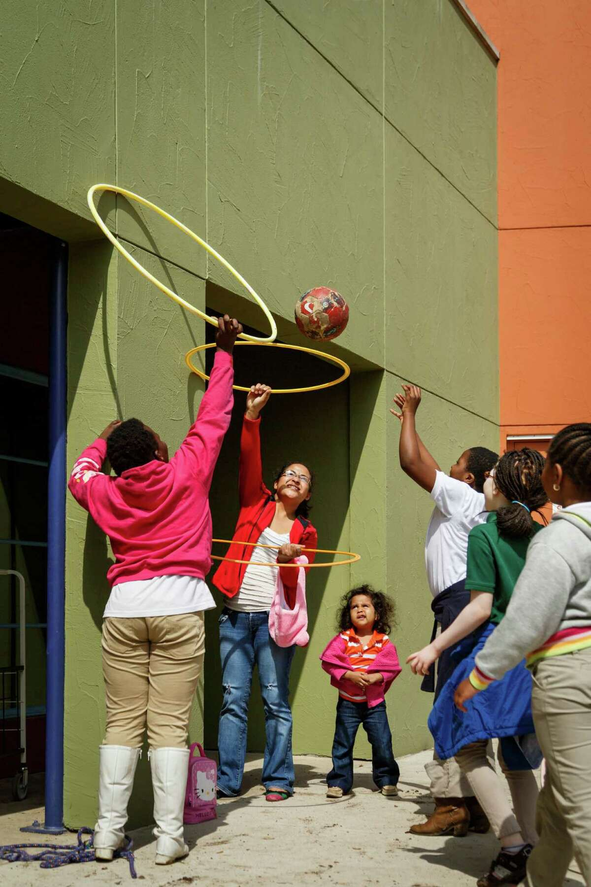 Volunteer Lorena Nolco, center holds up a hoola-hoop as her daughter Carla, 3, looks on at the Baker-Ripley Neighborhood Center, Monday, March 10, 2014, in Houston. The center provides a safe and friendly atmosphere for local residents to learn new things and an opportunity for them to participate in community activities. ( Michael Paulsen / Houston Chronicle )