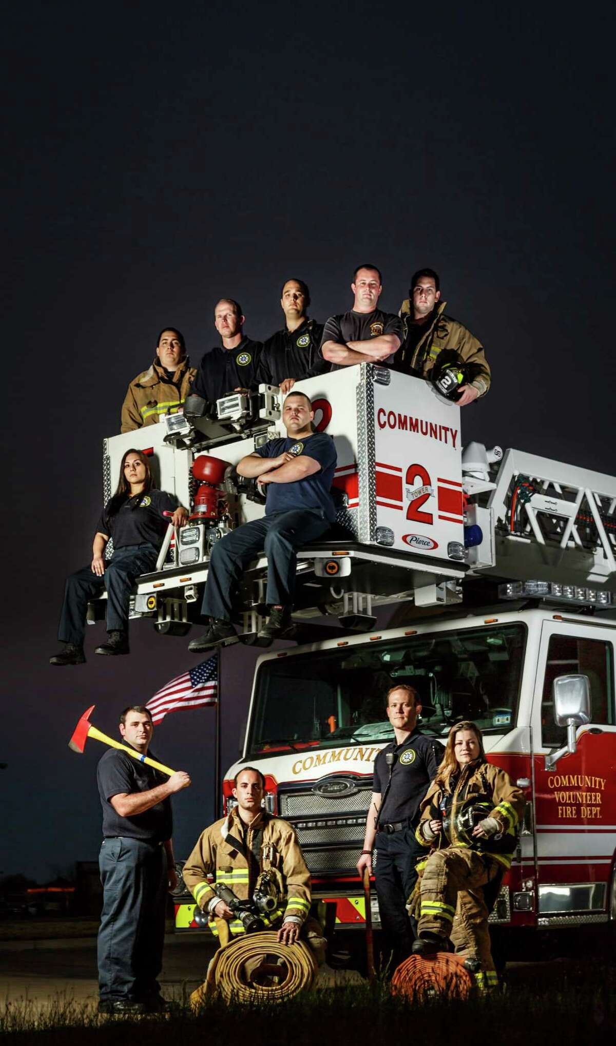 Will Wratney, left to right bottom, Dan Bridges, Brian Gazaway and Cindy Adams pose for a photo along with members of Station 1 and Station 2 of the Community Fire Department, a group of volunteer firefighters serving the Alief, Mission Bend, Katy and Cinco Ranch area, Tuesday, March 11, 2014, in Houston. ( Michael Paulsen / Houston Chronicle )