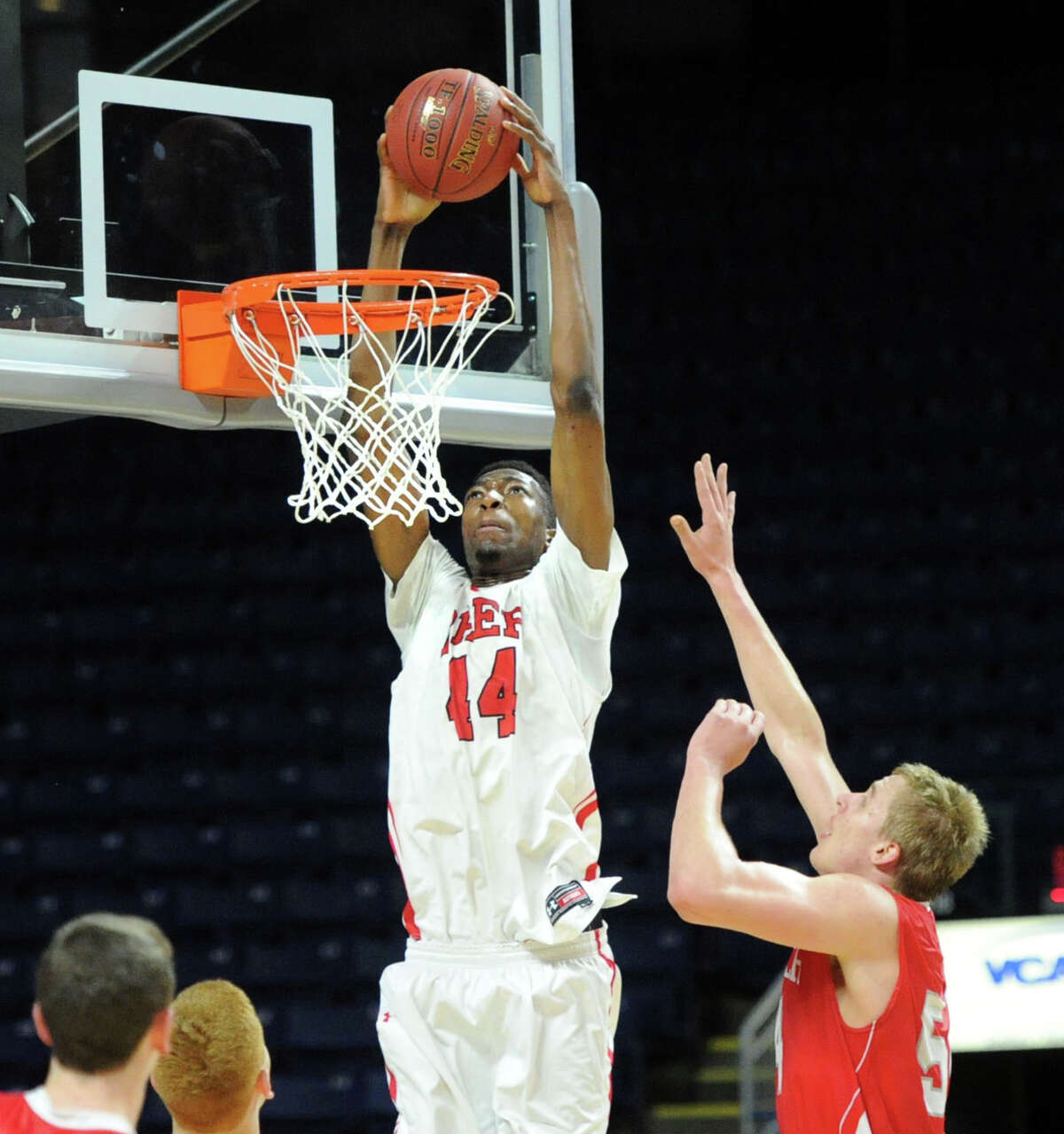 At left, Paschal Chukwu (#44) of Fairfield Prep gets past Alex Wolf (#54 ) of Greenwich to dunk during the Class LL boys basketball semi-final game between Fairfield Prep and Greenwich High School at the Webster Bank Arena in Bridgeport, Conn., Wednesday, March 19, 2014.