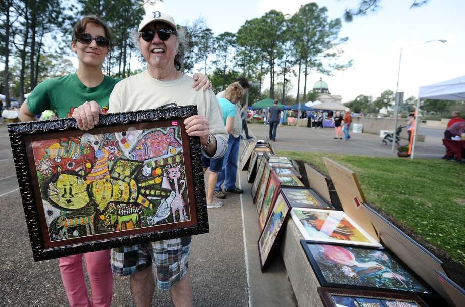 Meghan Sastre, left, and Dalle Bates, right, pose with some of Bates art during the Art in the Park event at Stark Park in Orange during the 2013 Orange County River Festival. Photo taken: Randy Edwards/The Enterprise