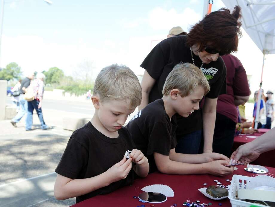 From left to right; Samuel, Zeke, and Kristi Richey make googly eyed fish at the Art in the Park event at Stark Park in Orange during the 2013 Orange County River Festival. Photo taken: Randy Edwards/The Enterprise