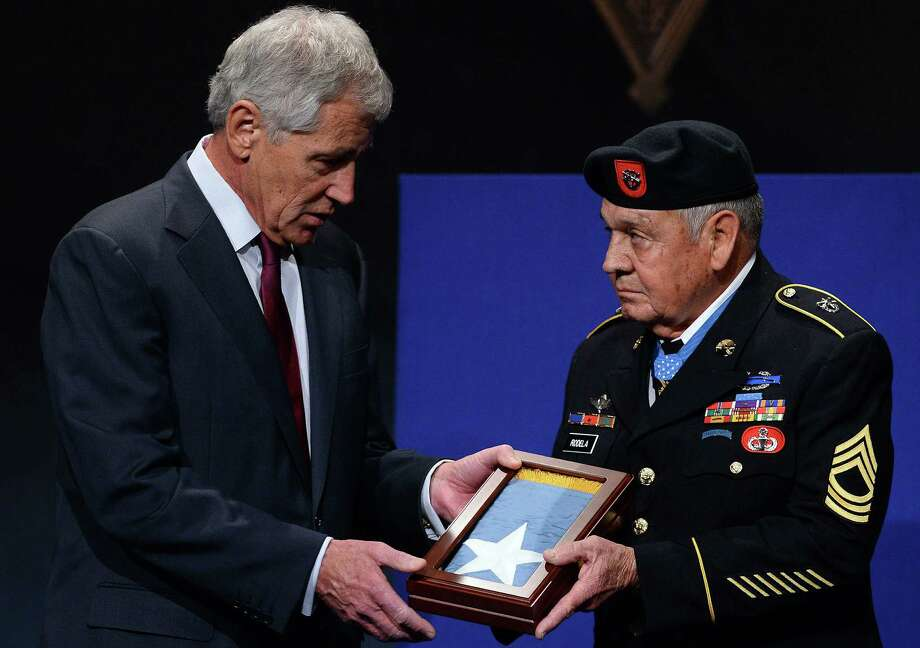 U.S. Defense Secretary Chuck Hagel  presents a crest to Medal of Honor recipient  Jose Rodela of San Antonio  during the  ceremony Wednesday. Photo: Photos By Jewel Samad / AFP / Getty Images / AFP