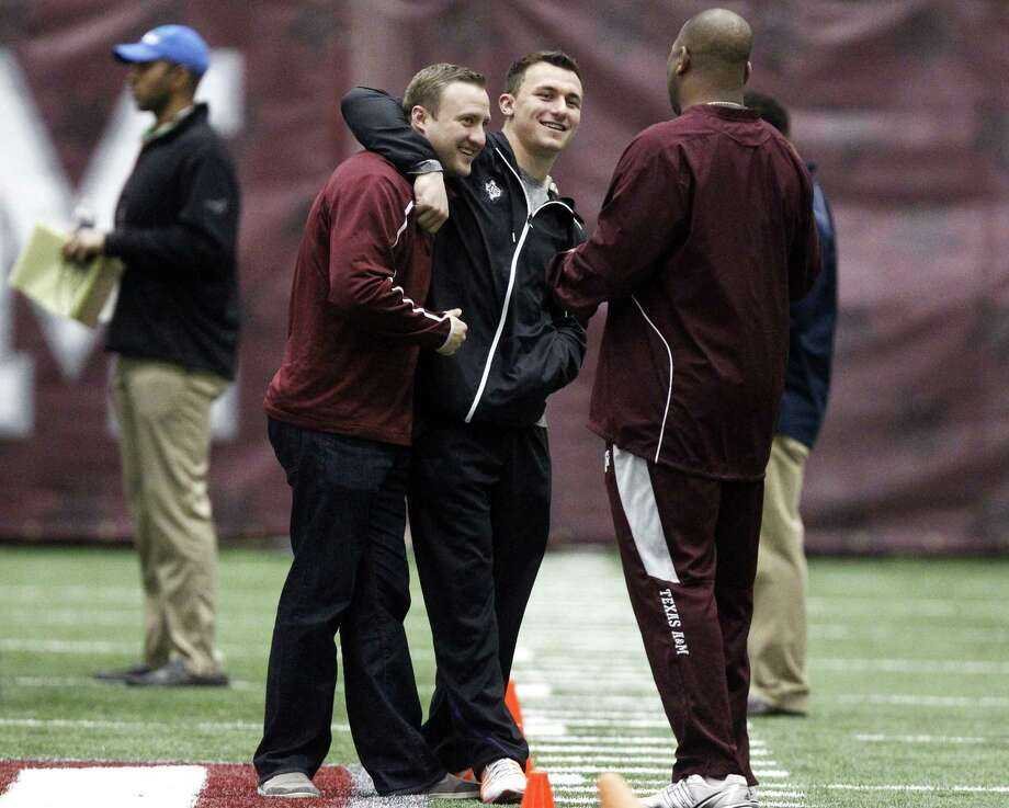 Texas A&M quarterback Johnny Manziel, middle, gives offensive coordinator Jake Spavital a hug during Texas A&M pro day held Wednesday, March 5, 2014, in College Station, Texas. (AP Photo/Patric Schneider) Photo: Patric Schneider, Associated Press / FR170473 AP