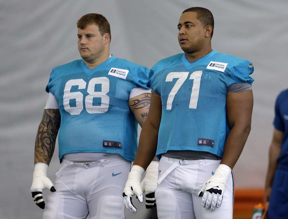 FILE - In this July 24, 2013, file photol, Miami Dolphins guard Richie Incognito (68) and tackle Jonathan Martin (71) stand on the field during NFL football practice in Davie, Fla. Martin, the offensive tackle at the center of the Dolphins' bullying scandal, has been traded to the San Francisco 49ers. The Dolphins announced the deal Tuesday night, March 11, 2014, on the first day of NFL free agency. Martin's move cross country brings him back to the Bay Area to be reunited with his former Stanford coach, Jim Harbaugh. (AP Photo/Lynne Sladky, File) Photo: Lynne Sladky, Associated Press
