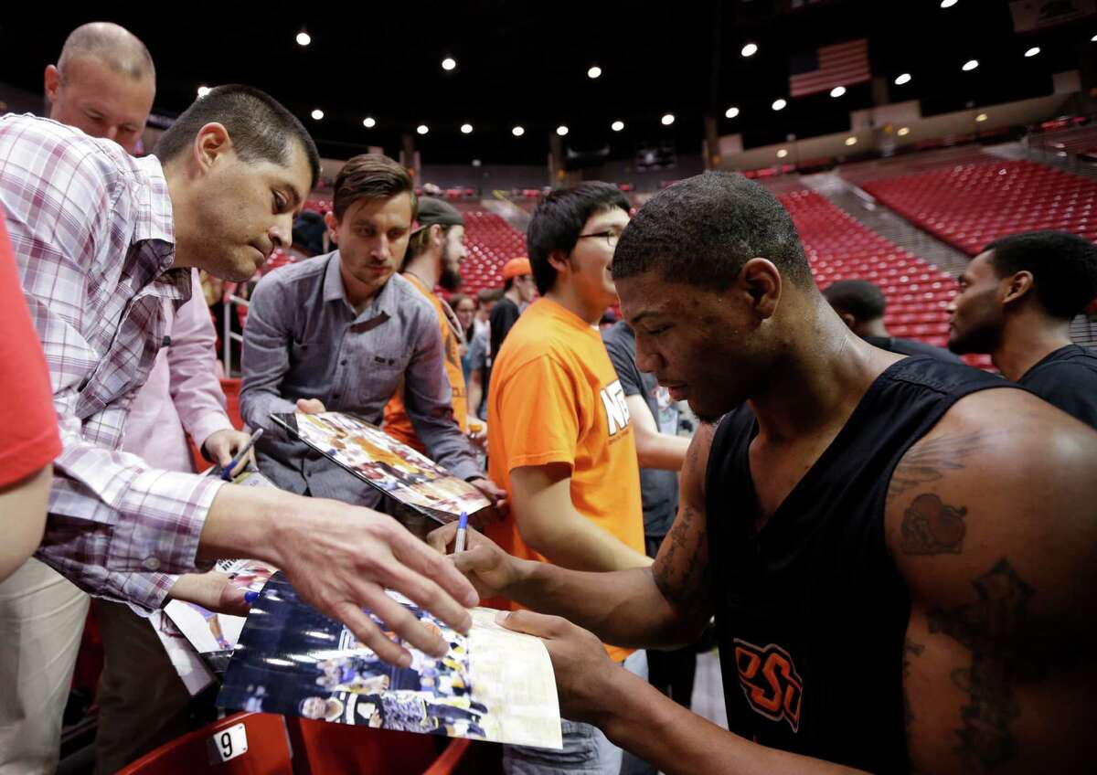 Oklahoma State guard Marcus Smart, right signs autographs during practice at the NCAA college basketball tournament Thursday, March 20, 2014, in San Diego. Oklahoma State faces Gonzaga in a second-round game on Friday. (AP Photo/Gregory Bull)
