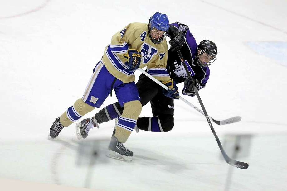 Newtown High School's #4 Dan Harrison gives pressure to Tri-Town's # 19 Jason Miller during Tuesday evening Division III State Tourament held at Ingallis Rink in New Haven. Photo: Mike Ross / Mike Ross Connecticut Post freelance -www.mikerossphoto.com