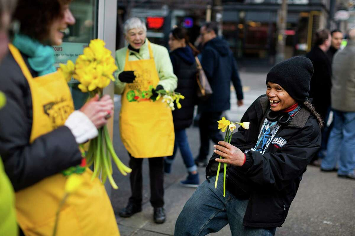 Sharon Jones, right, squeals with joy after receiving three of nearly 10,000 yellow daffodils from Pike Place Market employees and volunteers as a celebration on the first day of spring Thursday, March 20, 2014, in downtown Seattle. The generosity helped to spread spring cheer and raise public awareness of the flowers for sale at Pike Place Market.