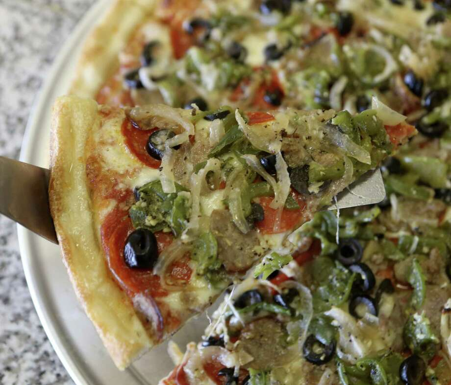 A fully loaded Supreme pizza at Poppy's includes pepperoni, sausage, onions, mushrooms, bell peppers and black olives on a thin crust. Photo: Photos By Helen L. Montoya / San Antonio Express-News / ©2013 San Antonio Express-News