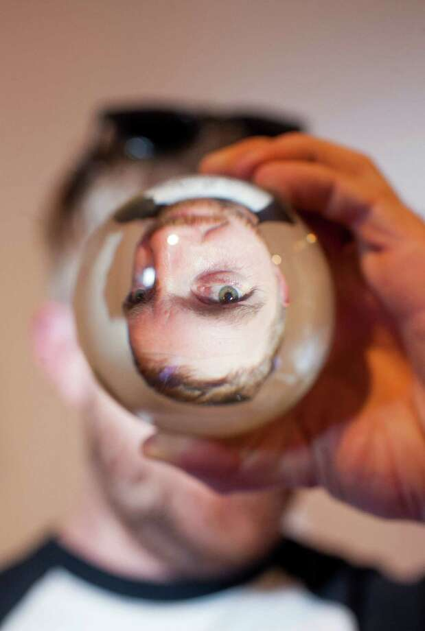 Jake Zollie Harper, glass blower and owner of Zollie Glass Studio, looks through a glass marble made in his studio. Photo: Julysa Sosa / For The Express-News / Julysa Sosa for the San Antonio Express-News