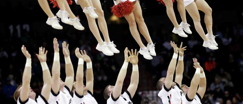 Cincinnati cheerleaders reach to catch other cheerleaders after tossing them into the air during a timeout in the second half during the second round of the NCAA men's college basketball tournament in Spokane, Wash., Thursday, March 20, 2014. Harvard won 61-57. (AP Photo/Elaine Thompson) Photo: Elaine Thompson, Associated Press / AP