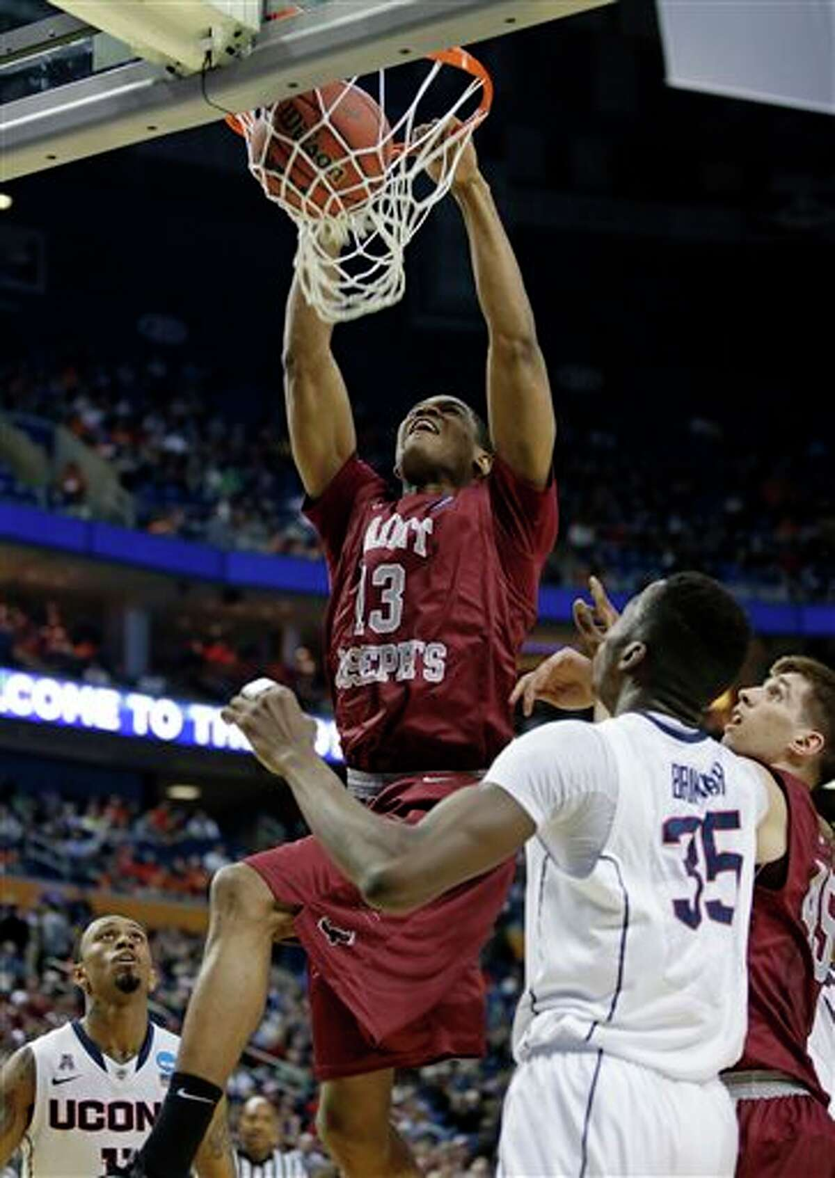 Saint Joseph's Ronald Roberts, Jr. (13) dunks the ball in front of Connecticut's Amida Brimah (35) during the first half of a second-round game in the NCAA college basketball tournament in Buffalo, N.Y., Thursday, March 20, 2014. (AP Photo/Nick LoVerde)