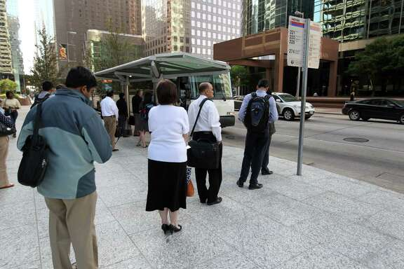 People line-up for the park and ride Grand Parkway METRO Bus 222 as it  stops at Louisiana and Mckinney in downtown Houston Thursday March 20, 2014.