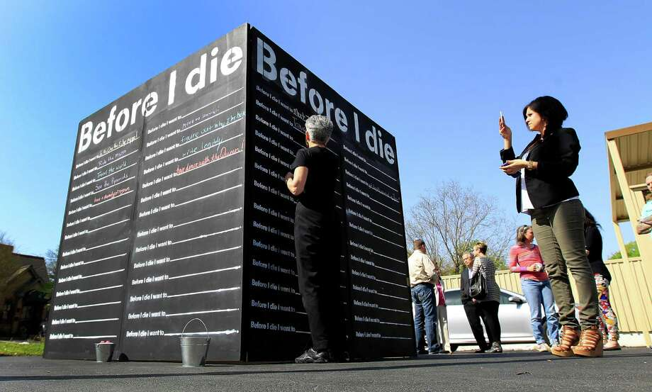 "Susan Farb Morris writes her bucket list item on the ""Before I Die"" bucket list wall set up at Distinctive Life Cremations and Funerals. Photo: Karen Warren, Houston Chronicle / © 2014 Houston Chronicle"