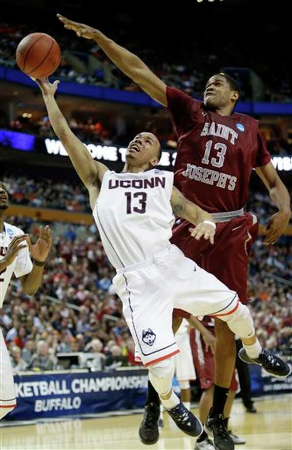 Connecticut's Shabazz Napier  (13) drives past Saint Joseph's Ronald Roberts, Jr. (13) during the  second half of a second-round game in the NCAA college basketball  tournament in Buffalo, N.Y., Thursday, March 20, 2014. (AP Photo/Nick  LoVerde)