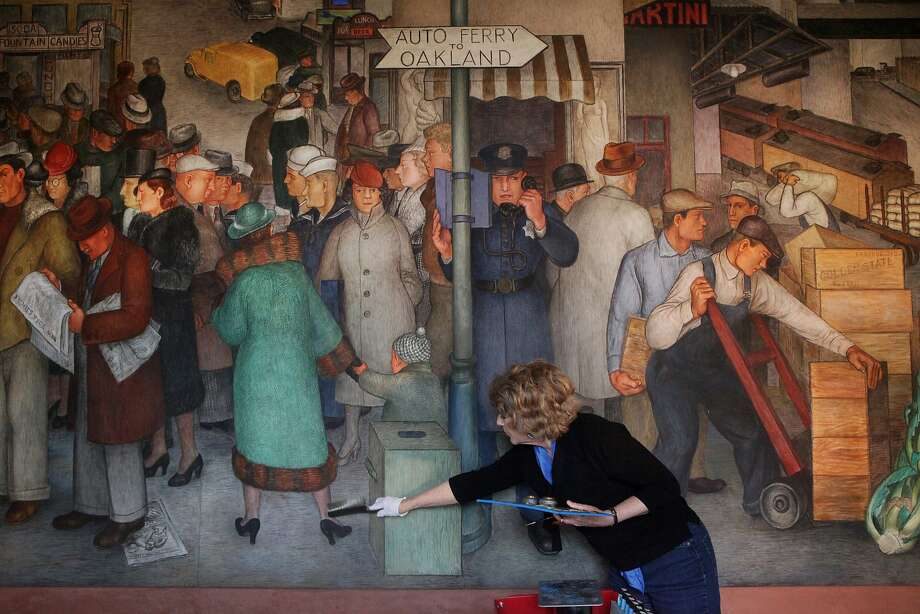 Anne Rosenthal works on a mural at Coit Tower. She has been using photographs of the murals in their original state to guide the restoration. Photo: Leah Millis, The Chronicle