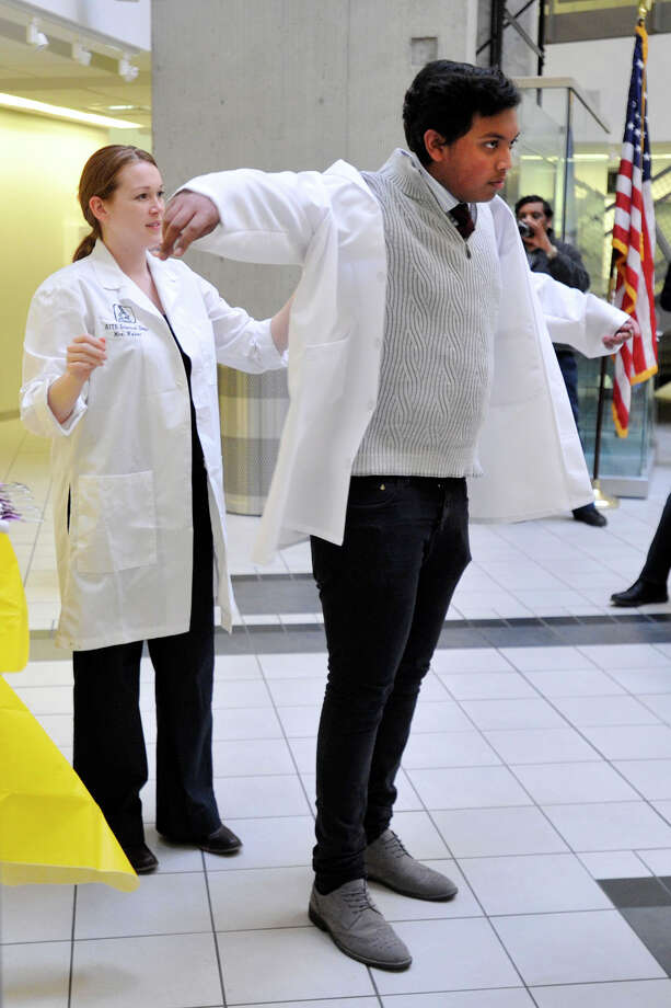 Lohith Annumala receives his white lab coat from Danielle Weber during Project Lead the Way's White Coat and Certification Ceremony at the Academy of Information Technology and Engineering in Stamford, Conn., on Thursday, March 20, 2014. Photo: Jason Rearick / Stamford Advocate