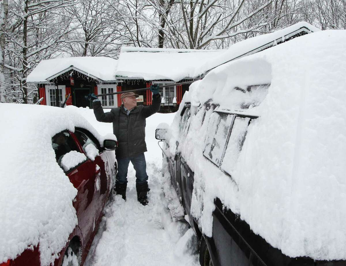 Donald Croteau works to clear nearly a foot of snow off his car on the first day of spring in North Woodstock, N.H. Forecasters are predicting a cooler-than-usual spring across the northern U.S.
