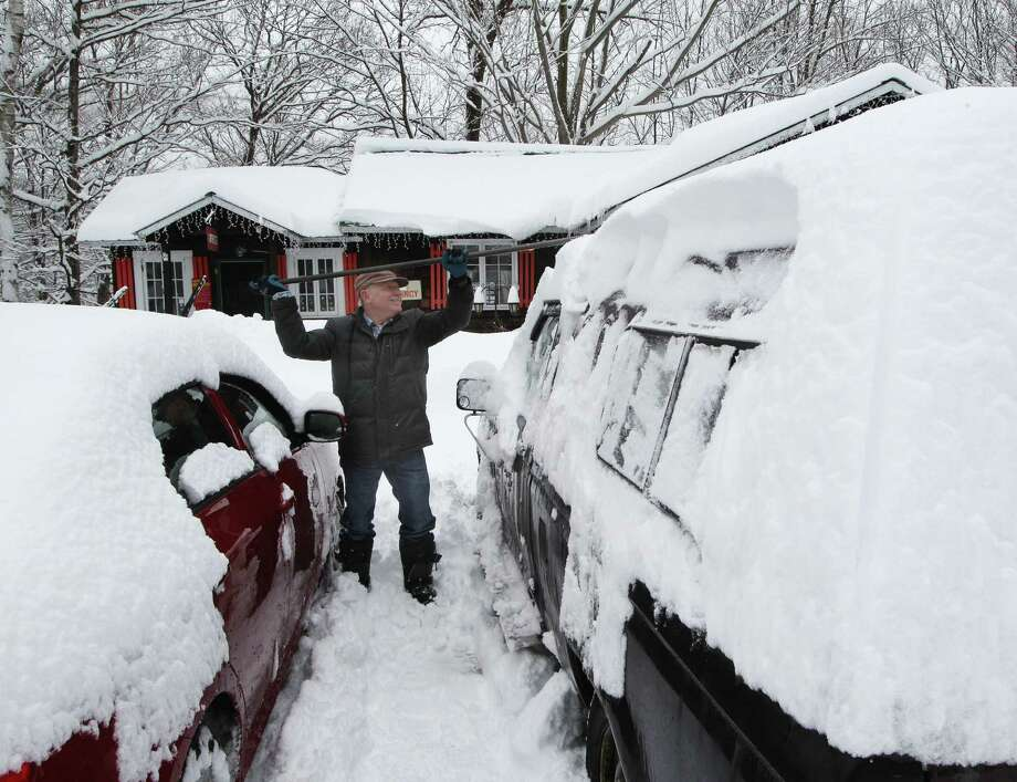 Donald Croteau works to clear nearly a foot of snow off his car on the first day of spring in North Woodstock, N.H. Forecasters are predicting a cooler-than-usual spring across the northern U.S. Photo: Jim Cole / Associated Press / AP
