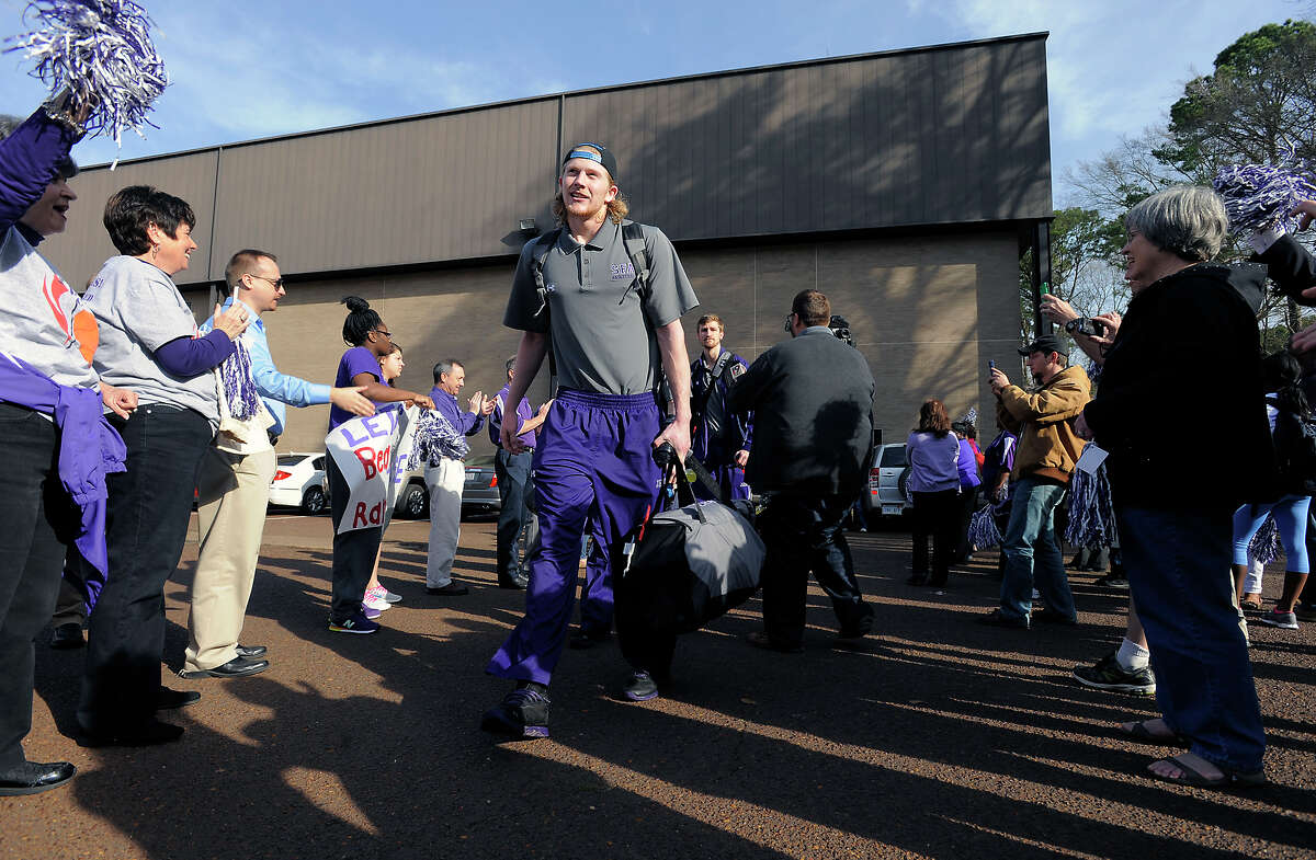 Fans send off Stephen F. Austin basketball player Jacob Parker, center, and teammates as they heads toward the bus Wednesday, March 19, 2014, in Nacogdoches, Texas, for the first leg of the Lumberjack's trip to San Diego, Calif., to face Virginia Commonwealth University in the second round of the NCAA men's basketball tournament. (AP Photo/The Daily Sentinel, Andrew D. Brosig) MANDATORY CREDIT