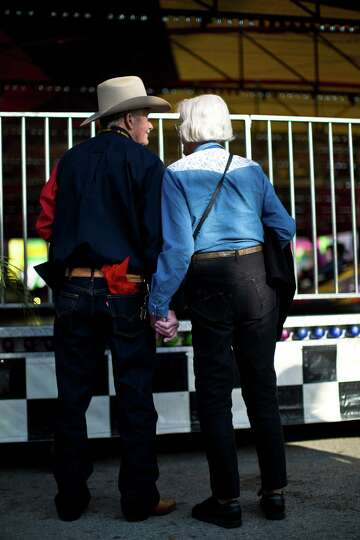 A couple holds hands as they walk around the Houston Livestock Show and Rodeo carnival before the ev