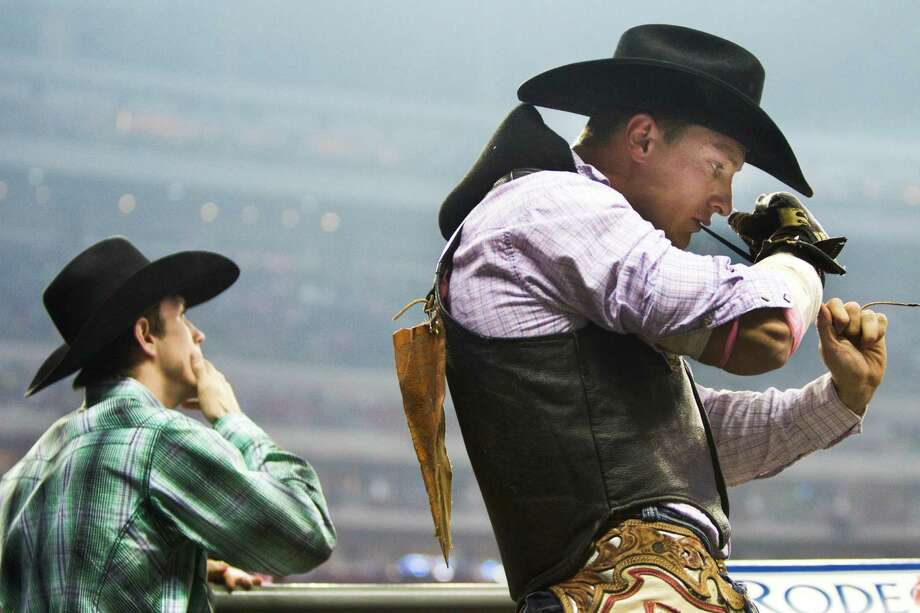 Yvan Jayne, 32, a bareback rider from the south of France, currently residing in Dallas, prepares his gloves for the BP Super Series Semifinal 1 at the RodeoHouston, Wednesday, March 19, 2014, in Houston. Jayne placed eighth on the Semifinal 1. Photo: Marie D. De Jesús, Houston Chronicle / © 2014 Houston Chronicle