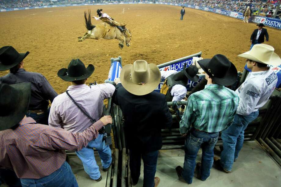 Winn Ratliff competes on the RodeoHouston semifinal 1 bareback competition, Wednesday, March 19, 2014, in Houston. Yvan Jayne, 32, waits for his turn on the horse he will be competing. Photo: Marie D. De Jesús, Houston Chronicle / © 2014 Houston Chronicle