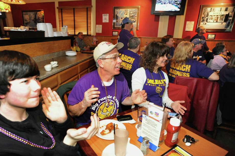 Liam Hurley, 16, left, and his parents Terry and Eileen Hurley of Guilderland join UAlbany basketball fans as they cheer on their team against Florida in NCAA action on Thursday, March 20, 2014, at the Across the Street Pub in Albany, N.Y. (Cindy Schultz / Times Union) Photo: Cindy Schultz / 00026227A