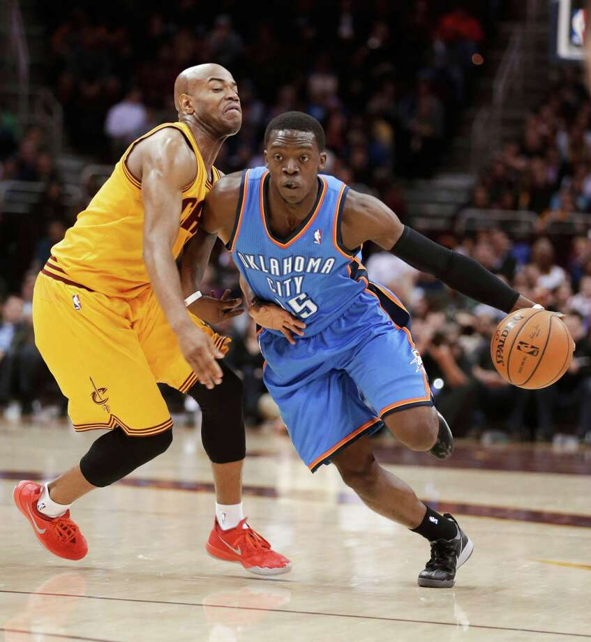 Oklahoma City Thunder's Reggie Jackson, right, drives past Cleveland Cavaliers' Jarrett Jack during the first quarter of an NBA basketball game Thursday, March 20, 2014, in Cleveland. (AP Photo/Tony Dejak) ORG XMIT: OHTD103 Photo: Tony Dejak / AP