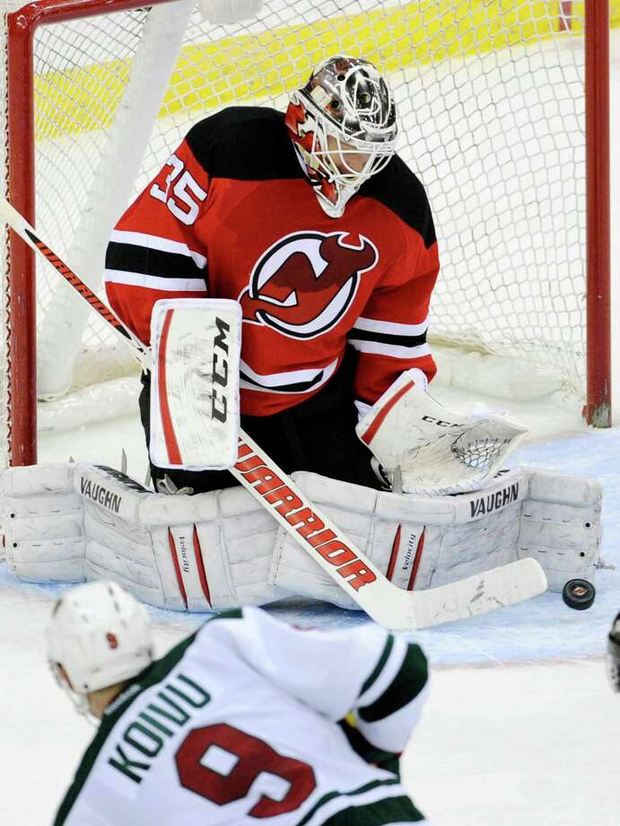 New Jersey Devils goaltender Cory Schneider deflects the puck as Minnesota Wild's Mikko Koivu (9) is near during the overtime period of an NHL hockey game Thursday, March 20, 2014, in Newark, N.J. The Devils won 4-3. (AP Photo/Bill Kostroun) ORG XMIT: NJBK111 Photo: Bill Kostroun / FR51951 AP