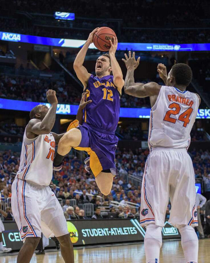 UAlbany Great Danes guard Peter Hooley (12) center, leaps for the basket against Florida Gators forward Dorian Finney-Smith (10) and Florida Gators forward Casey Prather (24) during the first half of the NCAA second round game, Thursday afternoon, March 20, 2014, in Orlando, FLA. (Gregory Fisher/Special to the Times Union) Photo: GF / SportsThroughTheLens.com