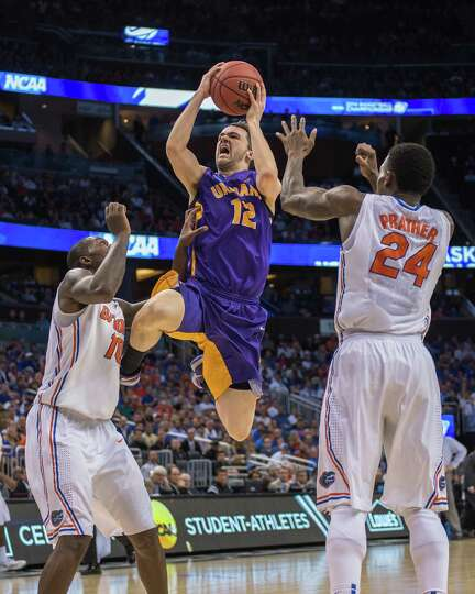 UAlbany Great Danes guard Peter Hooley (12) center, leaps for the basket against Florida Gators forw