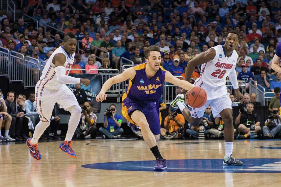 UAlbany Great Danes guard Peter Hooley (12) on the fast break with Florida Gators forward Will Yeguete (15) left and Florida Gators guard Michael Frazier II (20) right during the first half of the NCAA second round game, Thursday afternoon, March 20, 2014, in Orlando, FLA. (Gregory Fisher/Special to the Times Union) Photo: GF / SportsThroughTheLens.com