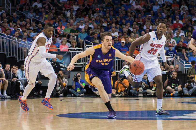 UAlbany Great Danes guard Peter Hooley (12) on the fast break with Florida Gators forward Will Yegue