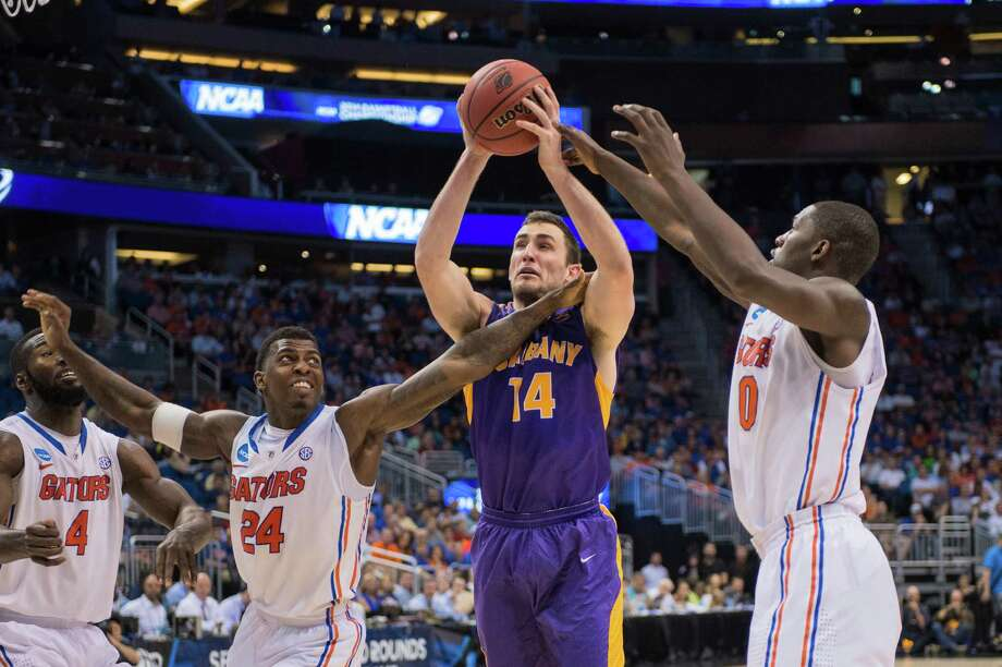 UAlbany Great Danes forward Sam Rowley (14) puts up a shot with Florida Gators center Patric Young (4) and Florida Gators forward Casey Prather (24) left and Florida Gators guard Kasey Hill (0) right, defending during the second half of the NCAA second round game, Thurday afternoon, March 20, 2014, in Orlando, FLA. (Gregory Fisher/Special to the Times Union) Photo: GF / SportsThroughTheLens.com