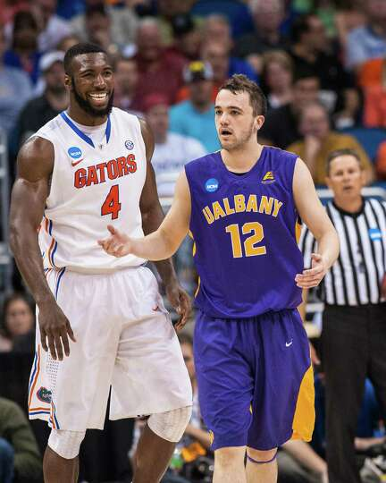 UAlbany Great Danes guard Peter Hooley (12) reacts to the kick block call with Florida Gators center