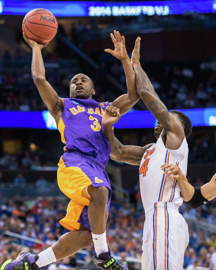 UAlbany Great Danes guard DJ Evans (3) left, puts up the leaping shot with  Florida Gators center Patric Young (4) right, defending during the 1st half of the NCAA second round game, Thurday afternoon, March 20, 2014, in Orlando, FLA. (Gregory Fisher/Special to the Times Union) Photo: GF / SportsThroughTheLens.com