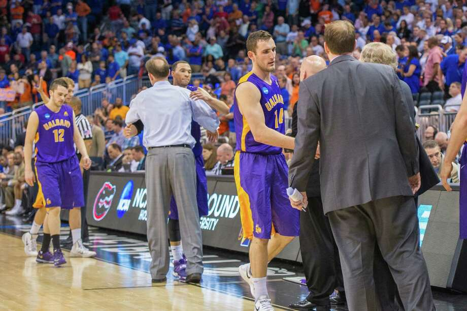 Great Danes guard Peter Hooley (12) walks off the court left,3 and UAlbany Great Danes head coach Will Brown embraces UAlbany Great Danes forward Gary Johnson (20) and UAlbany Great Danes forward Sam Rowley (14) shakes hands with his assistant coaches with seconds remaining in the 2nd half of the NCAA second round game, Thurday afternoon, March 20, 2014, in Orlando, FLA. (Gregory Fisher/Special to the Times Union) Photo: GF / SportsThroughTheLens.com