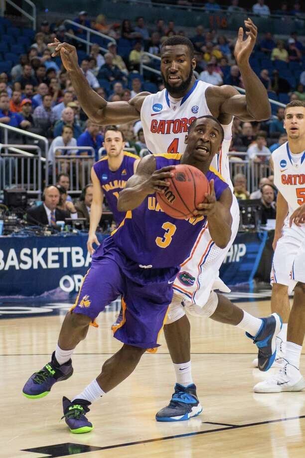 UAlbany Great Danes guard DJ Evans (3) drives to the basket with Florida Gators center Patric Young (4) defending during the first half of the NCAA second round game, Thurday afternoon, March 20, 2014, in Orlando, FLA. (Gregory Fisher/Special to the Times Union) Photo: GF / SportsThroughTheLens.com