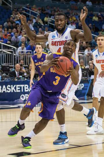UAlbany Great Danes guard DJ Evans (3) drives to the basket with Florida Gators center Patric Young