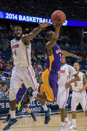 UAlbany Great Danes guard DJ Evans (3) right puts up the leaping shot with Florida Gators center Pat