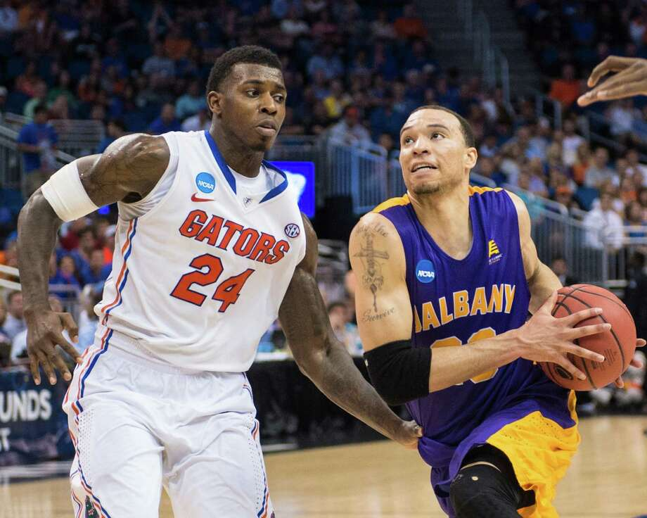 UAlbany Great Danes forward Gary Johnson (20) drives to the basket against Florida Gators forward Casey Prather (24) defending during the second half of the NCAA second round game, Thurday afternoon, March 20, 2014, in Orlando, FLA. (Gregory Fisher/Special to the Times Union) Photo: GF / SportsThroughTheLens.com