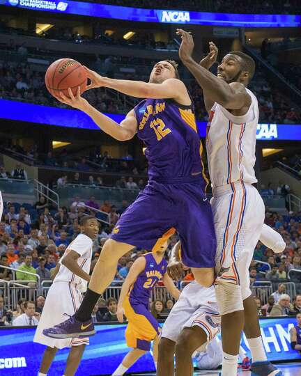 UAlbany Great Danes guard Peter Hooley (12) puts up a shot agasint Florida Gators center Patric Youn
